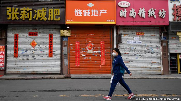 A woman walks past closed stores in Fengman District of Jilin City (picture-alliance/Xinhua/Y. Linyun)