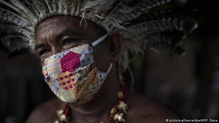 Homem indígena usando cocar e máscara