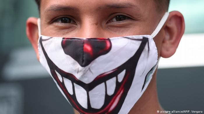 Ein Mann trägt eine Gesichtsmaske, die ein breites Grinsen zeigt