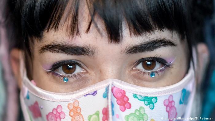 Gesichtsausschnitt einer Frau, nur die Augen und ein Teil des Mundschutzes sind zu sehen | Mundschutz durch Maske