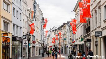 A street in Bonn's city center with sparse pedestrian traffic and red Beethovenfest banners (imago images/R. Oberhäuser)