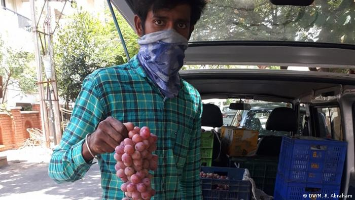 Farmer Chandra Gowda holding a bunch of grapes