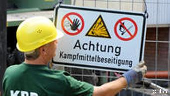 In Hanover a munitions disposal team member attaches a warning sign to a fence. Photo: Jochen Lübke dpa/lni