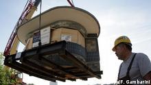JAHRESRÜCKBLICK NORDRHEIN-WESTFALEN - ARCHIV - Deutschlands wohl berühmtester Kiosk schwebt am Mittwoch (11.10.2006) im früheren Regierungsviertel in Bonn an einem Kran. Der Kiosk wird als Denkmal vorübergehend eingelagert. Der Pavillon wurde in seinem Rohbaukern auf Stahlträgern von seinem Standort vor dem früheren Kanzleramt und dem Bundestagsgebäude auf einen Schwertransporter verladen. Der ovale Kiosk war 50 Jahre lang ein Teil der Bonner Republik, wo sich auch die Politiker versorgten. Der Kiosk musste jetzt den Bauarbeiten für ein großes Kongresszentrum weichen, das auch für UN-Konferenzen dienen soll. Er soll in etwa zwei Jahren ganz in der Nähe im Regierungsviertel wieder in seinem Originalzustand aufgebaut werden. Foto: Federico Gambarini dpa/lnw +++(c) dpa - Bildfunk+++ | Verwendung weltweit
