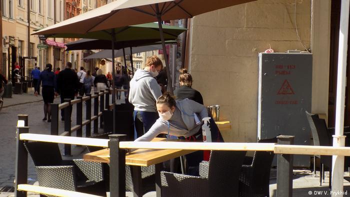 Працівниця ресторану у Львові дезінфікує стіл на вуличній терасі закладу (фото з архіву)
