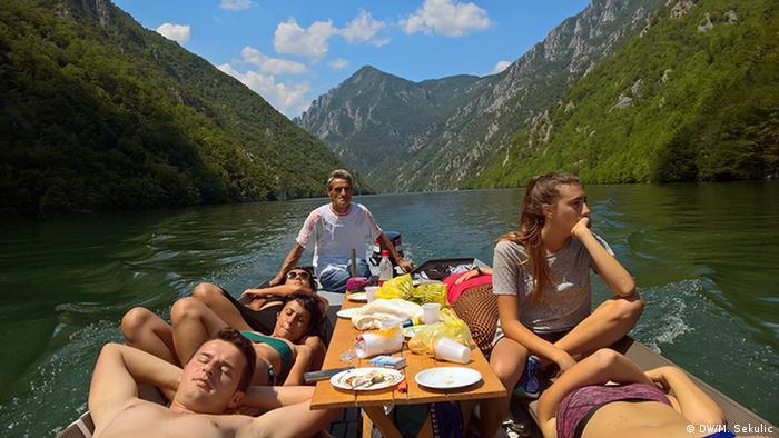 Turisti u vožnji čamcem starog Huse na jezeru Perućac
