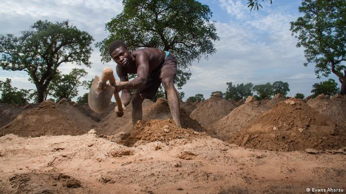 A man in Ghana digs earth mounds to dig for yams.