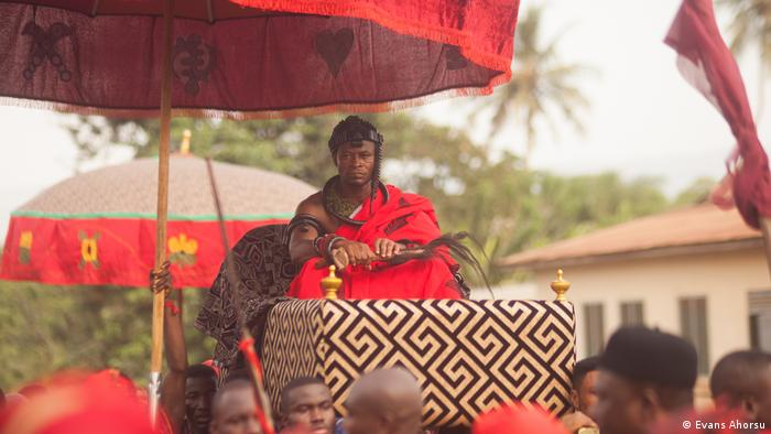 The chief, wearing a red robe, is carried on a litter above people's shoulders