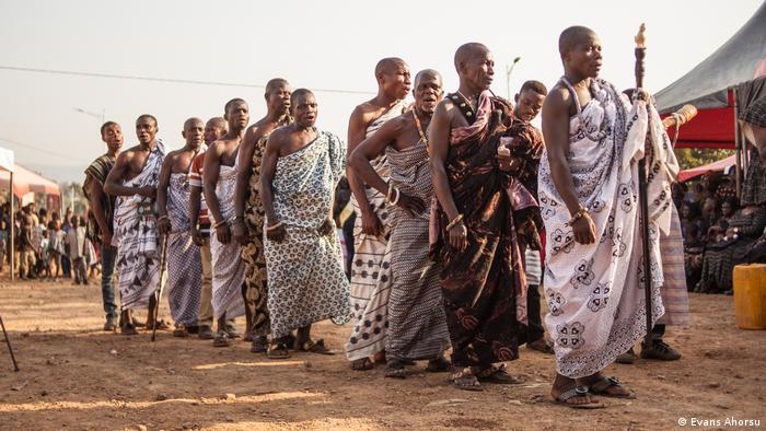 Ghanaian men wearing traditional cloth stand in a line waiting