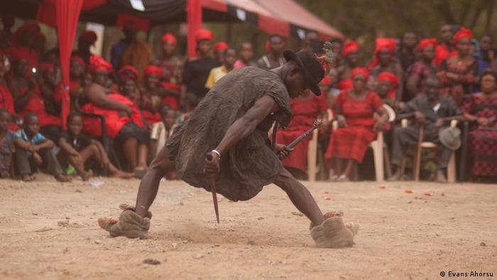 A Ghanaian man dances energetically in front of a crowd