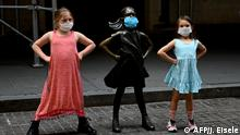 Two young girls with face masks next to a sculpture with a mask