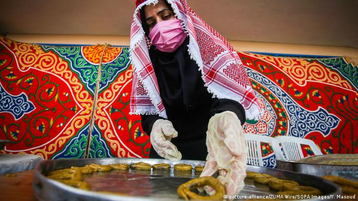 A Palestinian woman wearing a protective mask and hand gloves, makes traditional cakes (picture-alliance/ZUMA Wire/SOPA Images/Y. Masoud)