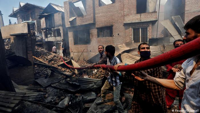 People hold a hosepipe amidst the smoldering debris of residential houses that, according to local media reports, were damaged during a gun battle between Indian security forces and suspected militants, in Srinagar May 19, 2020.