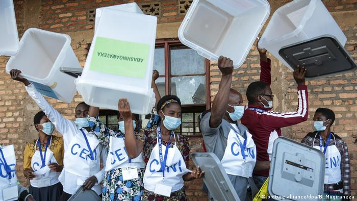 Election officials hold up ballot boxes to show they are empty before voting begins