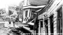 Valdivia, Chile. Buildings are twisted into grotesqu shapes along this street in Valdivia after another earthquake hit, 27th May 1960, Chile Chile / Mono Print |