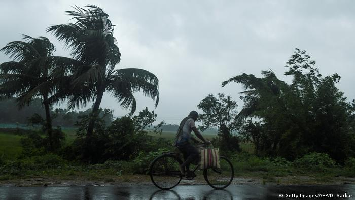 A man cycles through the rain in West Bengal