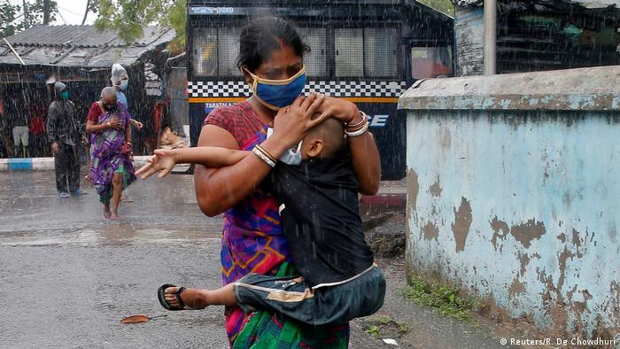 Mulher tenta proteger filho da tempestade em Calcutá