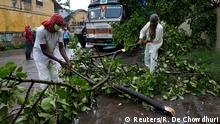 Rescue workers cut tree branches that fell on a truck trailer after heavy winds caused by Cyclone Amphan, in Kolkata, India, May 20, 2020. REUTERS/Rupak De Chowdhuri