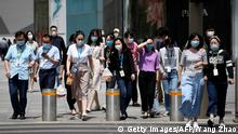 People wearing face masks amid concerns of the COVID-19 coronavirus cross a street in Beijing on May 20, 2020. (Photo by WANG ZHAO / AFP) (Photo by WANG ZHAO/AFP via Getty Images)