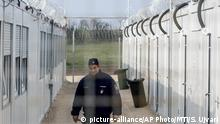 FILE - In this Thursday, April 6, 2017 file photo a Hungarian police officer patrols the enlarged transit zone set up for migrants at the Hungary's southern border with Serbia near Tompa, 169 kms southeast of Budapest, Hungary. Hungary's government says it is shutting down the transit zones on its southern border with Serbia where asylum-seekers are being kept while their asylum requests are decided. (Sandor Ujvari/MTI via AP, file) |