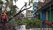 A man cuts branches of an uprooted tree after Cyclone Amphan made its landfall, in Kolkata, India, May 21, 2020. REUTERS/Rupak De Chowdhuri TPX IMAGES OF THE DAY