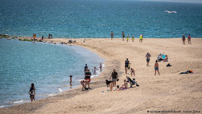 Отдыхающие в защитных масках, призванных защитить их от заражения коронавирусом, на пляже в Барселоне