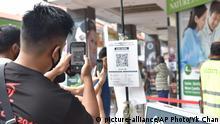 Singapur Mann scannt QR-Code eines digitalen Abfertigungssystems
