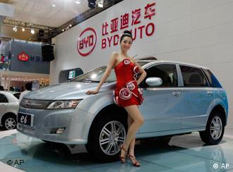 A model poses next to a new BYD e6 electric vehicle of Chinese automaker BYD Auto at the Shanghai International Auto Show