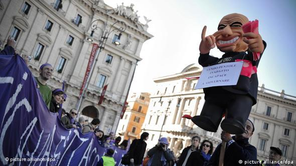Protestors hold up critical Berlusconi effigy