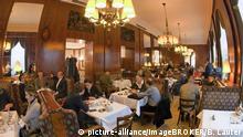Gäste sitzen im Café Landtman in Wien an Tischen mit weißen Tischtüchern