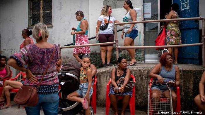 Mulheres sentadas e em pé aguardam em fila em favela no Rio de Janeiro