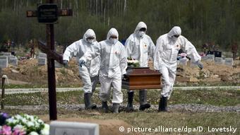 Санитары в спецодежде несут гроб на кладбище