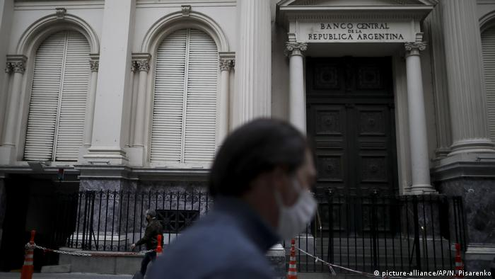 Men walk in front of the central bank at the financial district during a government-ordered lockdown to curb the spread of COVID-19 in Buenos Aires,
