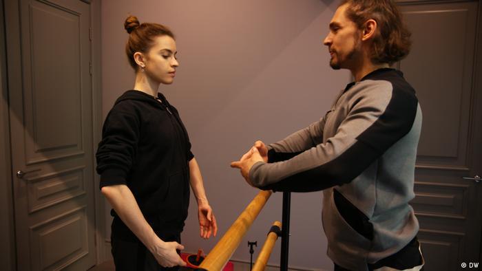 Bailarino e bailarina treinam na barra