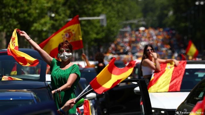A demonstrator wearing a protective face mask waves a Spanish flag during a drive-in protest organised by Spain's far-right party Vox (Reuters/S. Perez)