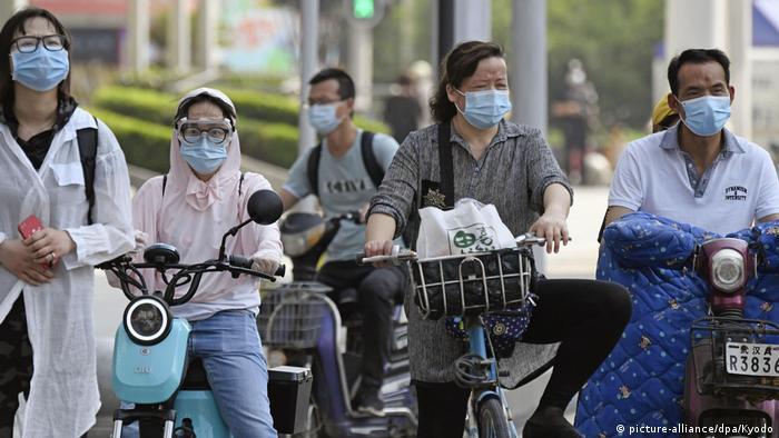 China Wuhan Menschen mit Mundschutz auf den Straßen (picture-alliance/dpa/Kyodo)