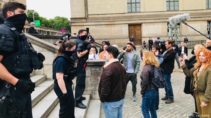 Attila Hildmann mit Mikrofon bei einer Kundgebung, umgeben von Zuschauern und Polizei - wenig später wird er festgenommen