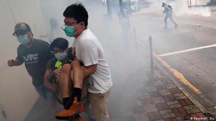 Homens de máscara carregam rapaz em meio a fumaça gerada por gás lacrimogêneo