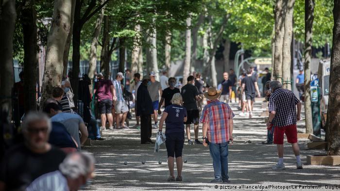Pessoas caminham em parque de Paris