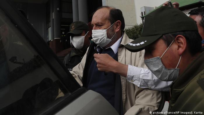 Bolivian Health Minister Marcelo Navajas is transported to court, wearing a face mask