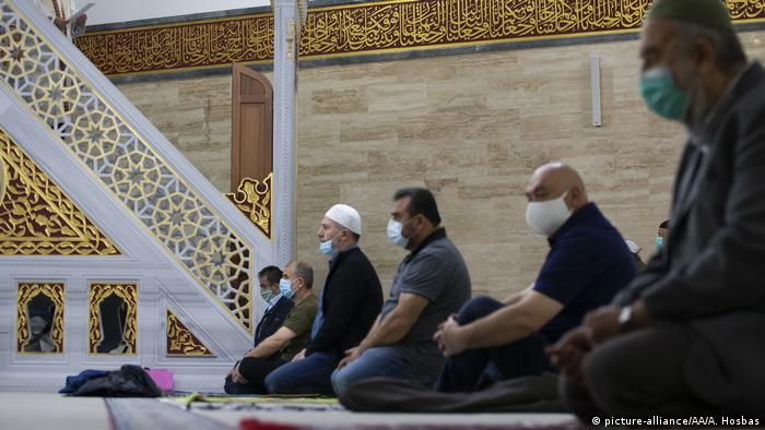 Muslims wearing protective masks take part in an Eid al-Fitr prayer at a mosque in Berlin, Germany