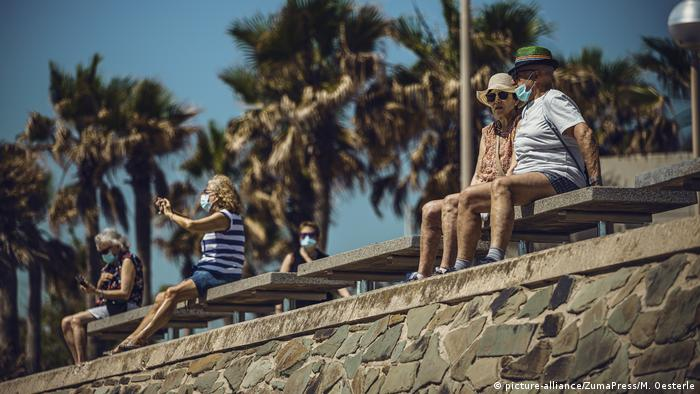 Elderly commuters wearing protective face masks enjoy the view over Barcelona's beach