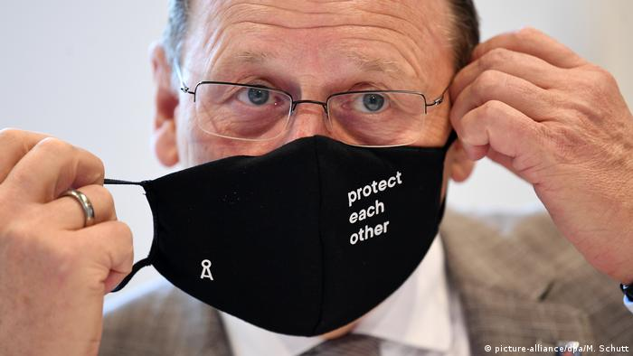 Bodo Ramelow putting on a face mask (picture-alliance/dpa/M. Schutt)
