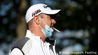 Мужчина курит со спущенной маской