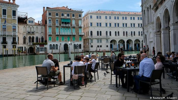 Tourists have lunch at a restaurant by the Grand Canal in Venice