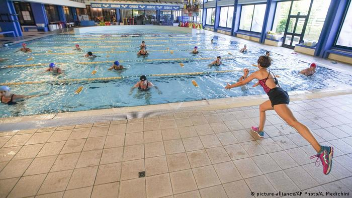 An instructor conducts a water gym lesson in the indoor swimming pool of the Forum sports center (picture-alliance/AP Photo/A. Medichini)