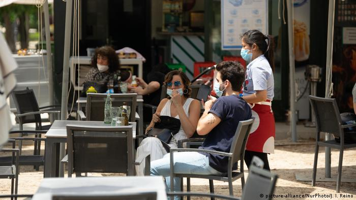 Customers wearing protective face masks sit at an outdoor terrace table of a bar and cafe in Madrid