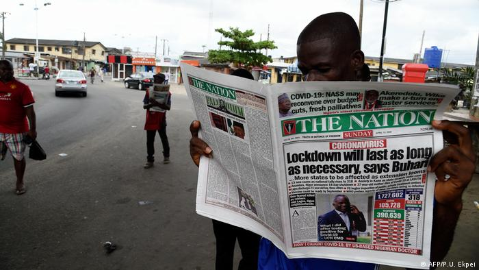 A man reads a newspaper at a newsstand in Lagos to know more about the extended lockdown as part of measures to prevent the spread of COVID-19 coronavirus. Across the globe, media outlets face economic challenges in the wake of the crisis.