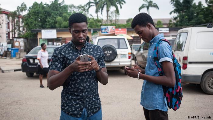 Young Nigerian men using Smartphones (AFP/S. Heunis)