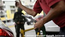 A worker holds a gas pump at a PDVSA state oil company gas station in Caracas, Venezuela, Monday, May 25, 2020. The first of five tankers loaded with gasoline sent from Iran this week is expected to temporarily ease Venezuela's fuel crunch while defying Trump administration sanctions targeting the two U.S. foes. (AP Photo/Matias Delacroix) |
